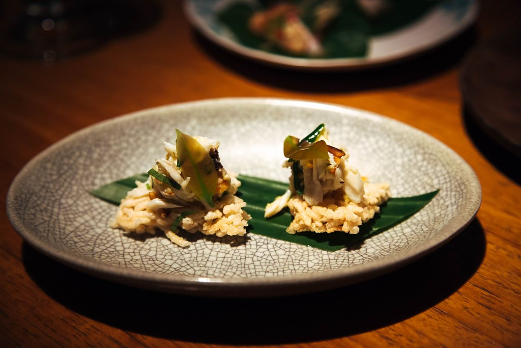 Blue swimmer crab with peanuts and pickled garlic on rice cakes